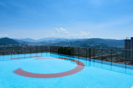 A swimming pool located on a tall building. The swimming pool is located at the edge of the building. The background consists of nature landscape, mountain, and some low density apartment buildings. Stockfoto