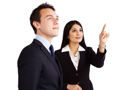 A young business woman is pointing while a young business man is looking up.