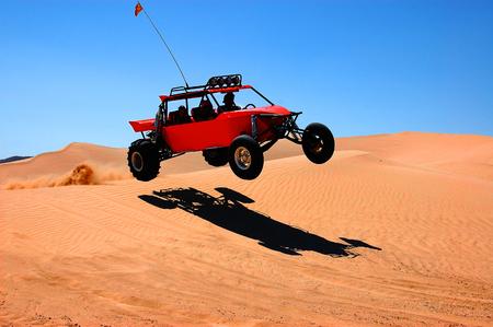 Dunebuggy saltando sobre una duna de arena en el Valle de la Muerte, California Foto de archivo