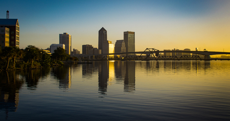 sunrise reflected off the buildings downtown jacksonville florida with bridges over the st johns river in the foreground