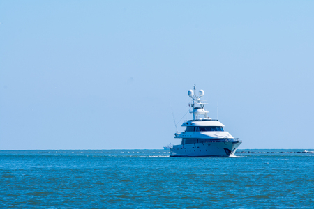 White luxury yacht entering St Augustine inlet on calm blue seas.