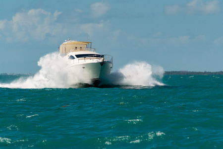 white luxury yacht crashing through bow waves while cruising in the florida keys