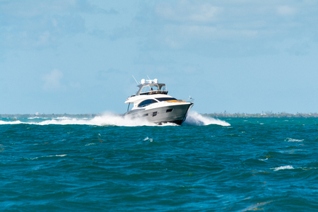 white luxury motorboat breaking through bow waves while cruising in the florida keys