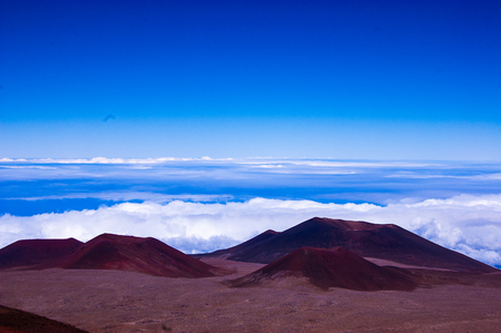 Red volcanic landscape of mauna kea with clouds in background