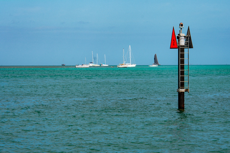 red 2 navigation marker in key west harbor with sailboats anchored in background