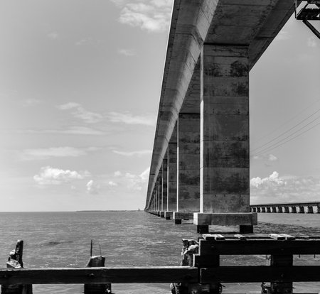 monochrome image of one span of the seven mile bridge on the way to key west in the florida keys from the water