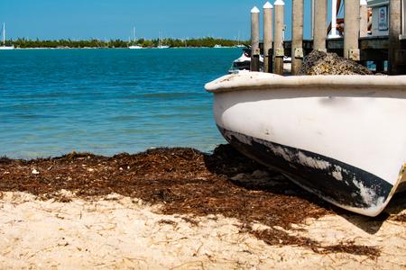 white rowboat on white sand beach in key west harbor florida