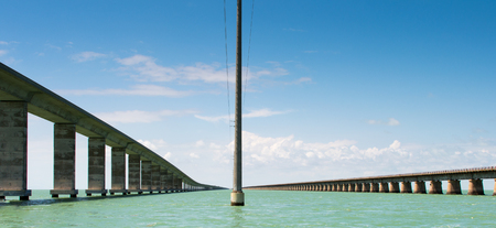 pole in center between two spans of the seven mile bridge in the florida keys from the water