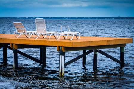wooden deck with white chairs over the st johns river Фото со стока