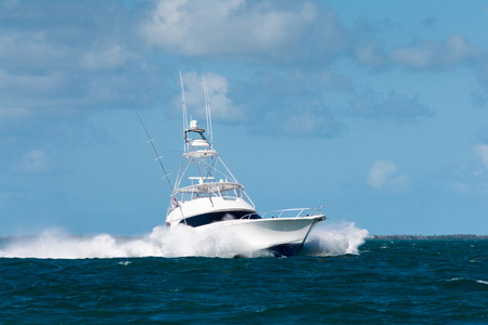 white fishing boat with large bow waves in the florida keys 스톡 콘텐츠