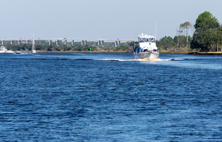 white trawler cruising down florida river on a sunny day