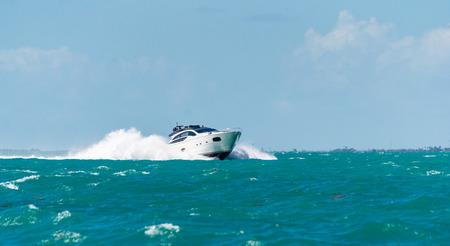 white powerboat splashing through waves in the florida keys