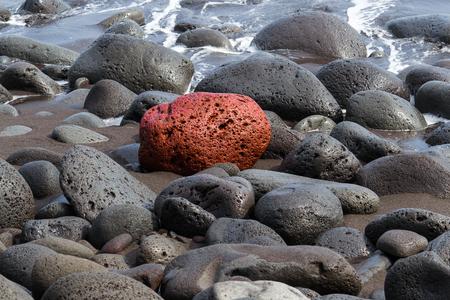 Red Lava Rock In Field Of Black Rocks