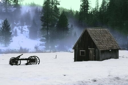 Barn and old wooden wagon in the snow photo
