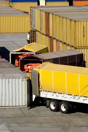 loading cargo containers from trucks photo