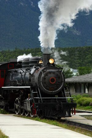 steam locomotives: steam engine train pulling out of the station Stock Photo
