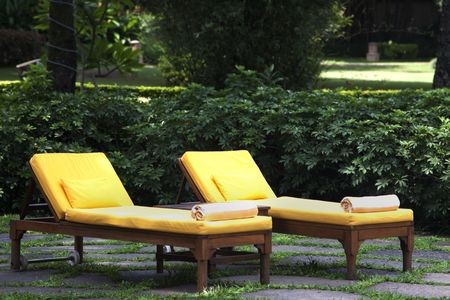 lounge: Two yellow lounge chairs on a patio Stock Photo