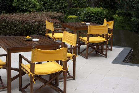 wood tables and yellow chairs on an outside patio by a pond Stock Photo - 5678836
