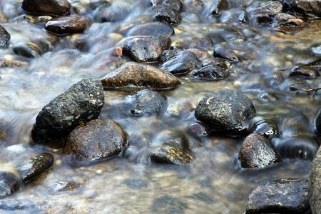 Water stroomt over rotsen in een stroom  Stockfoto