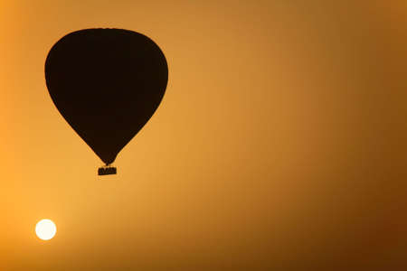A hot air Balloon backlit by the rays of the morning Sun.  photo