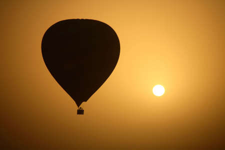 A hot air Balloon backlit by the rays of the morning Sun.   - Luxor - Egypt Stock Photo
