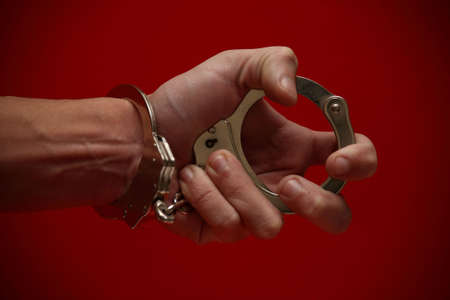 A really expressive photograph of a hand (handcuffed) holding the other end of the cuffs, on a red background! :) photo