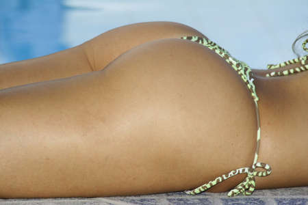 A photograph of a brazilian womans buttocks and back, next to a swimming pool!
