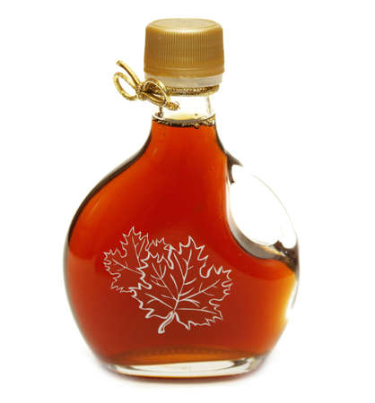 A small bottle of maple syrup with the maple leaves printed on the front and a nice golden ribbon on the neck! Stock Photo - 801521