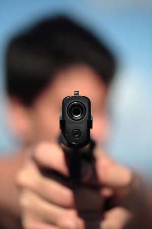 robust: A young, robust man, in his 20s with dark hair pointing 2 pistols to the camera. Stock Photo