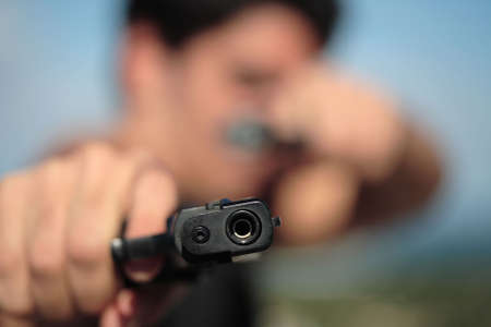 delinquent: A young, robust man, in his 20s with dark hair pointing 2 pistols to the camera. Stock Photo