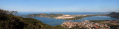 polis: A panoramic image of a far view of a city lake with the ocean as a background. This is Lagoa da Concei��o in Florian�polis, Brazil.