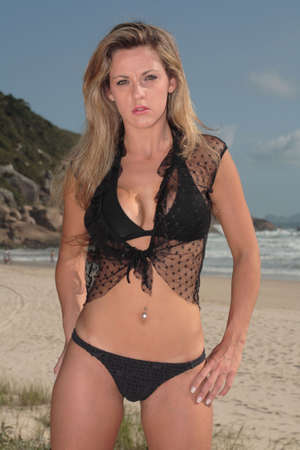 A blonde, 20-30 year old female model on the beach, in Florianópolis - Brazil. This is part of a series. Have a look at the other photos of this model in various outfits and poses. Stock Photo