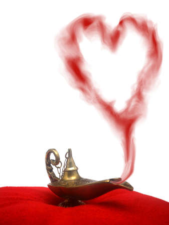 A magical genie lamp with smoke on a red velvet pillow with a heart shaped smoke. Standard-Bild