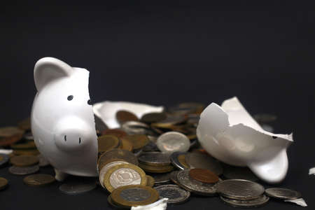 A broken piggy bank isolated on a dark background with loads of coins from around the world. photo