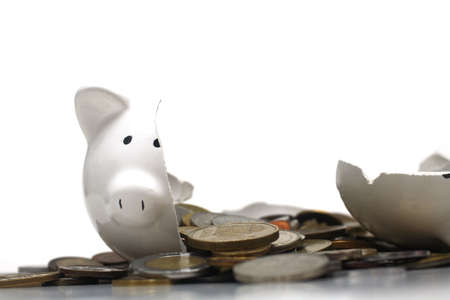 A broken piggy bank isolated on a white background with loads of coins from around the world. photo