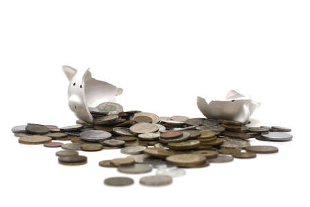 A broken piggy bank isolated on a white background with loads of coins from around the world.