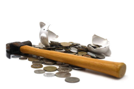 A broken piggy bank isolated on a white background with loads of coins from around the world and a hammer.