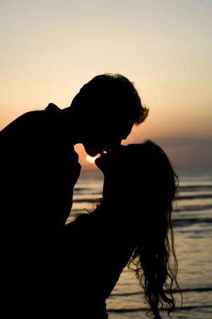beso labios: Una silueta de una pareja a punto de besar.  Foto de archivo