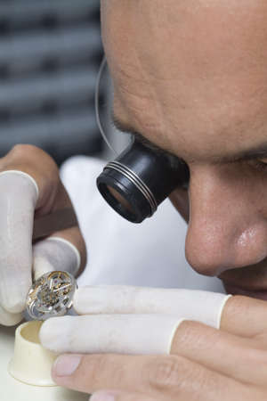 watchmaker: A watchmaker or repair man in action, viewing very closely a swiss watch.