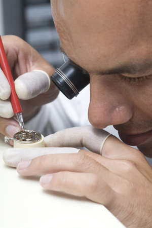 A watchmaker or repair man in action, viewing very closely a swiss watch. photo