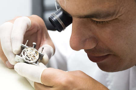 A watchmaker or repair man in action, viewing very closely a swiss watch.