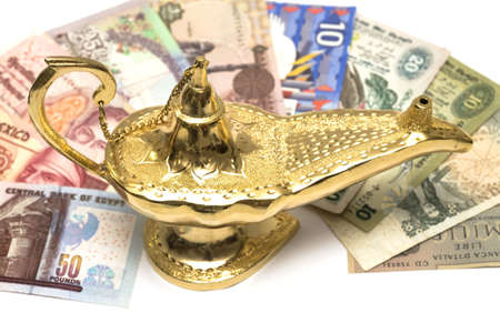 alladdin: An arabic magic lamp, isolated on white, with loads of money from around the world. Stock Photo