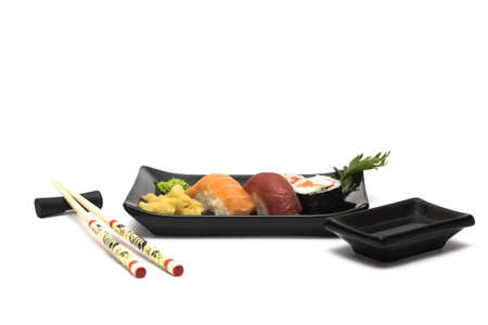hashi: A set of sushi on a black plate with wasabi and gari, isolated on a white background, wish hashi ans soy sauce. Stock Photo