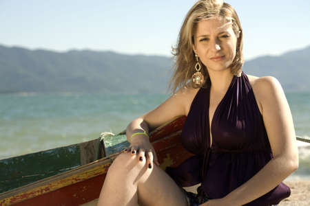 A very pretty and young blond brazilian woman wearing a purple blouse next to a fisherman's boat, at the beach. Stock Photo - 4903111