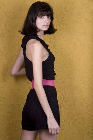 18 year old: An 18 year old exotic brazilian model, with short dark hair, a young looking face and a skinny body. She is wearing a black dress and pink belt. Stock Photo