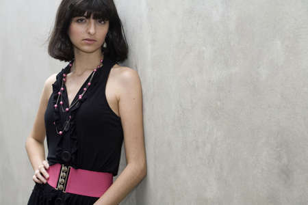 18 year old: An 18 year old exotic brazilian model, with short dark hair, a young looking face and a skinny body. She is wearing a black dress and pink belt. Plenty of copyspace in the image.