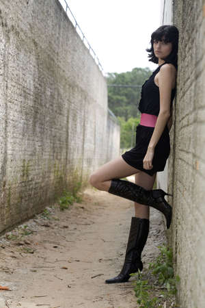 18 year old: An 18 year old exotic brazilian model, with short dark hair, a young looking face and a skinny body. She is wearing a black dress and pink belt and black leather boots.