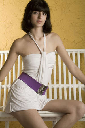 18 year old: An 18 year old exotic brazilian model, with short dark hair, a young looking face and a skinny body. She is wearing a white dress and purple belt, on a white bench in front of a yellow, textured wall. Stock Photo