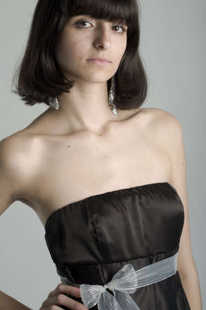 18 year old: An 18 year old exotic brazilian model, with short dark hair, a young looking face and a skinny body. This was shot in a studio and shes weariing a black, strapless dress. Stock Photo