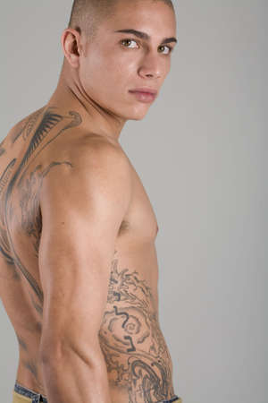 A young, muscular brazilian man in a studio shot on a gray background.